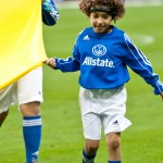A child wearing an Allstate Insurance jersey helps carry a flag onto the field at a Mexican National Futbol Team match
