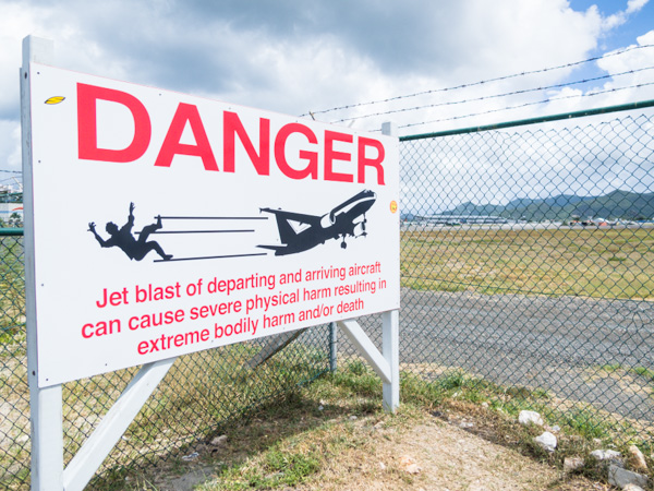 A warning to pedestrians and cars on the road that separates the runway and beach on Sint Maarten