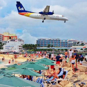 A Liat Air Dash-8 lands over the beach on to Runway 10 at Princess Juliana Airport on Sint Maarten