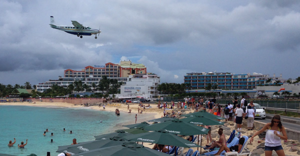 A small commuter/cargo plane lands over the beach on to Runway 10 at Princess Juliana Airport on Sint Maarten