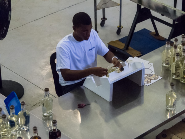 Labels being applied by hand to individual bottles of rum at the John Watling's Distillery on Nassau