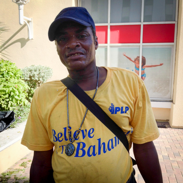 A working man wears a shirt featuring the slogan of the PLP party in the Bahamas