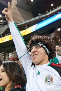 A fan stands to support the Mexico Men's National Futbol Team in Houston in 2012, sporting a wig gotten from Allstate in their fan village. Event Photography by Ari Shapiro - AShapiroStudios.com